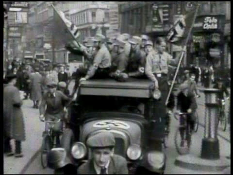 Truck full of Nazi Germans driving down street w/ Swastika flags MS Putting up posters on store windows MS Sign in German 'Jews Forbidden' WS...