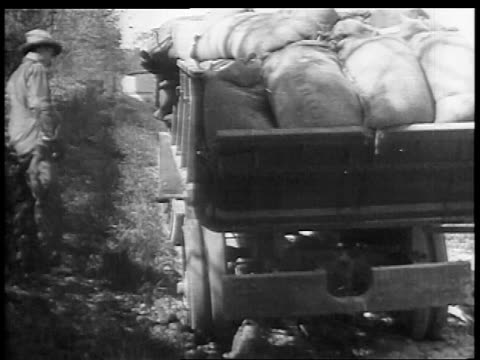 B/W 1927 REAR VIEW truck loaded with sacks stuck on country road as farmer looks on / educational