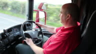 Truck / Lorry driver in cab, driving on the road
