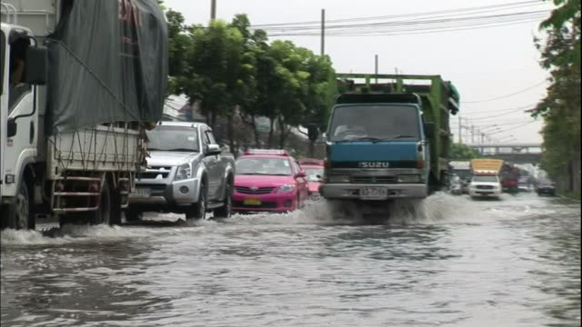 A truck splashes flood water as it drives on a Bangkok highway