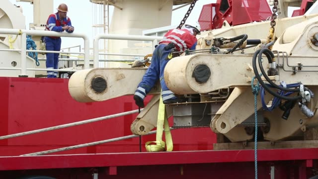 A truck stands parked alongside offshore pipelay vessel Deep Energy operated by Technip SA as a section of shallow water roller box is unloaded for...