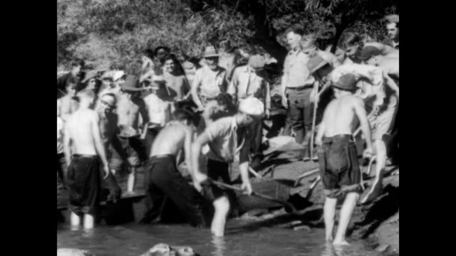 / truckloads of men and boys of the Civilian Conservation Corps arrive at river side to begin panning for gold / hundreds of boys standing in the...