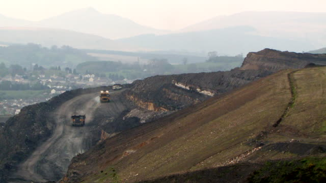 WS Trucks and water bowser operating in opencast mine with town and brecon beacons national park  / Ffos-y-fran / Merthyr Tydfil, Glamorgan/Wales, United Kingdom