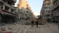 Trucks clear the rubble of Dar alShifa Hospital after it was bombed in Aleppo Syria