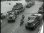 Trucks transporting British tanks on road HA WS Trucks pulling trailers w/ tanks motorcycles WS Army trucks leaving motor pool MS Horse pulling...