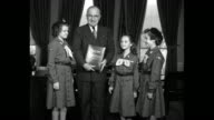 Truman stands with three uniformed Girl Scouts in Oval Office they give threefingered salutes all shake hands as he holds leather binder the girls...