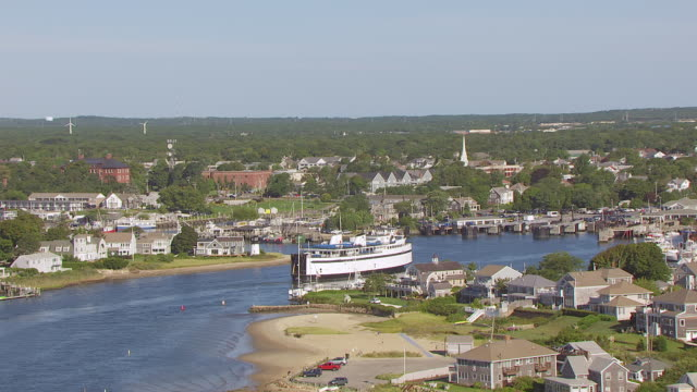 WS AERIAL POV Tug boat moving in sea with town in background / Hyannis, Massachusetts, United States