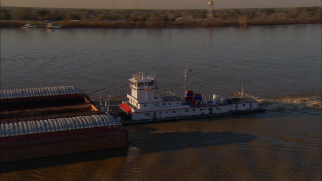 AERIAL WS Tugboat and barges traveling on Mississippi River near Gramercy Bridge / Gramercy, Louisiana, USA