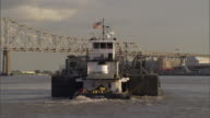 A tugboat pushes a barge toward a bridge in downtown New Orleans.