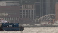 A tugboat pushes a trash barge up the Hudson river.  New york city is featured behind.