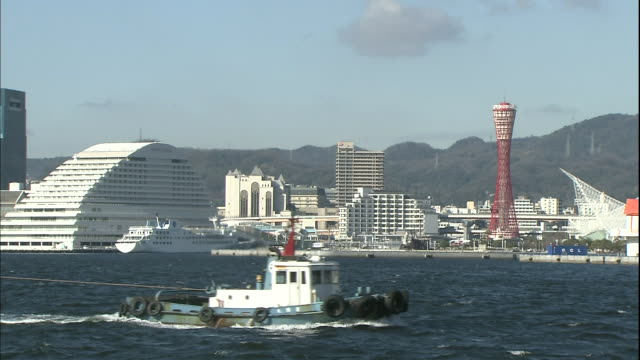 A tugboat tows a barge in the harbor at the Port of Kobe.