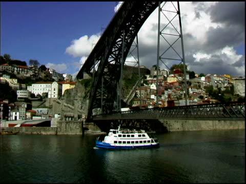 Tugboat under bridge on Douro river in Porto Portugal