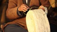 Tunisian Basket Maker weaves basket in traditional way