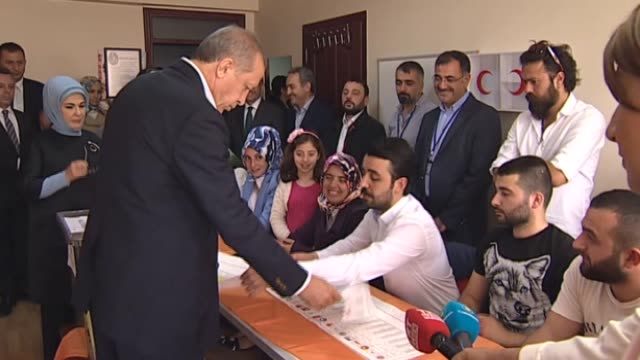 Turkey's President Recep Tayyip Erdogan and his wife Emine Erdogan cast their ballot in the Turkish general election at a polling station in Istanbul...