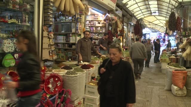 Turkish men women and children pass through souk the includes herbs food gifts scarves purses and other products