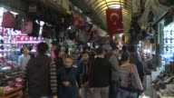 Turkish men women and children shop at souk that offers shoes backpacks high heels and other products
