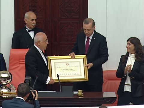Turkish Parliament Speaker Cemil Cicek delivers a speech as he presents certificate of election to Turkish Presidentelect Recep Tayyip Erdogan during...