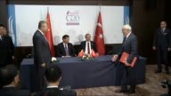 Turkish President Recep Tayyip Erdogan and Chinese President Xi Jinping look on as Chinese and Turkish officials sign documents during the Treaty...