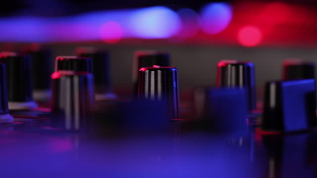 ECU SELECTIVE FOCUS DJ turning knob at turntable in nightclub, view of hands / London, United Kingdom