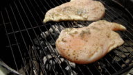 Turning over Two Grilled Chicken Breast On A Grill