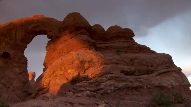 Turret Arch with dramatic morning sunshine and shadows across it's face - pan