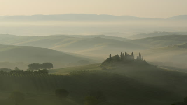 Tuscany, series of foggy hills with a farm at sunrise, static shot.