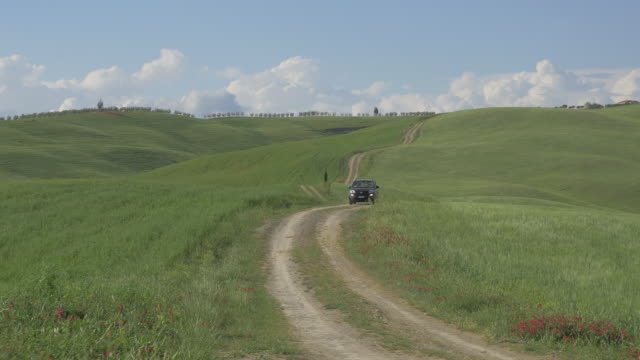 Tuscany,a dirt road going up and down on a series of hills and a car moving in.