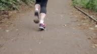A twenty-something young woman jogs along a path through woodland.