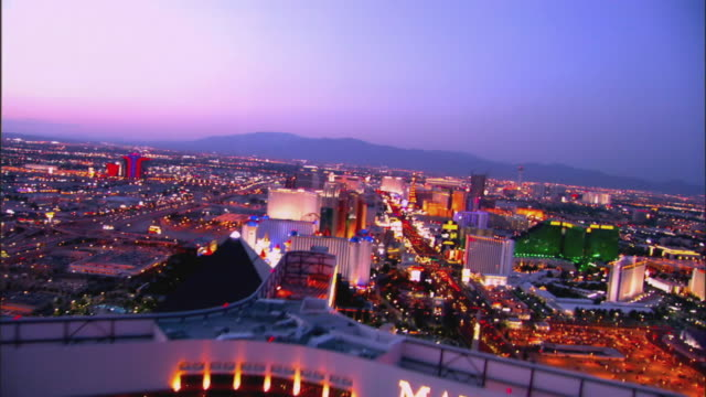 twilight aerial across roof top of Mandalay Bay Hotel Casino and over to Las Vegas Strip and down into sphinx at Luxor  / Las Vegas, Nevada, USA