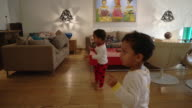 Twin boys dancing their heart out, elders look on, handheld gimbal