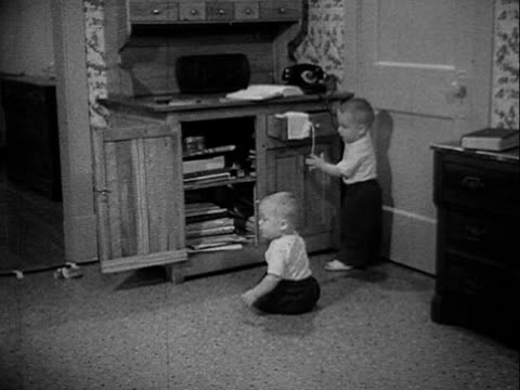 Twin boys playing w/ hutch cabinet w/ open door open drawer [SOT Dr Spock saying tired mother calls this 'getting into everything' tone of voice says...