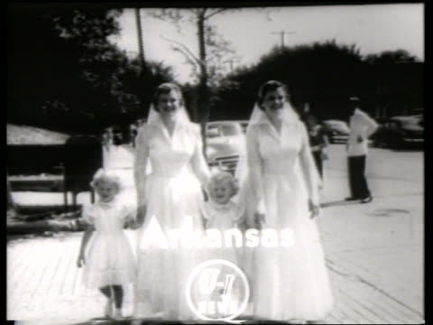 B/W twin brides walking with young twin girls on sidewalk / Title in shot / NO SOUND