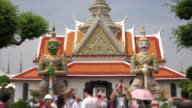 Twin giants stand guard at the entrance to Wat Arun in Bangkok, Thailand (people blurred for commercial use)