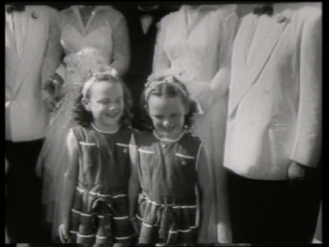 B/W twin girls standing in front of 2 bride and grooms / NO SOUND