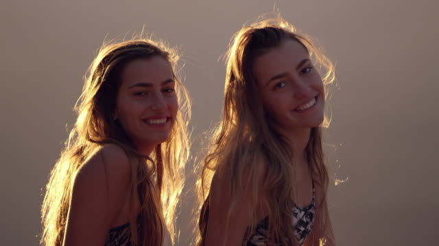 Twin teenage girls laughing and smiling