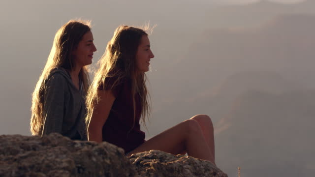 Twin teenage girls talking and pointing sitting on rocky edge