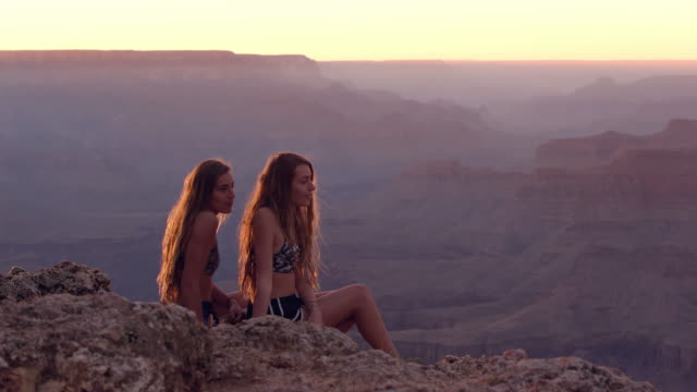 Twin teenage sisters overlooking canyon as one helps the other to stand up