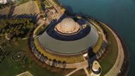 Twisting aerial of Adler Planetarium, soaring out over Chicago Harbor to show skyline