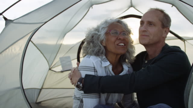 Two Adventurous Seniors Snuggling in Their Tent