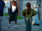 Two African American girls with braids play hopscotch in street, New Orleans