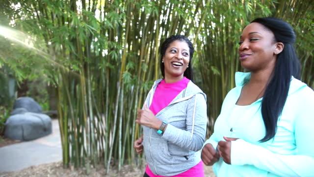 Zwei afroamerikanische Frauen Powerwalking im park