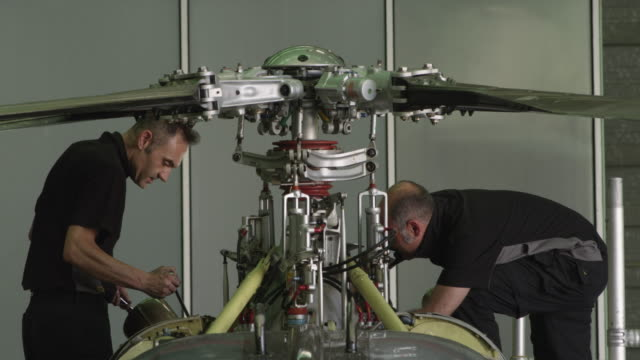 LS two aircraft mechanics working on rotor mast of helicopter, RED R3D 4K