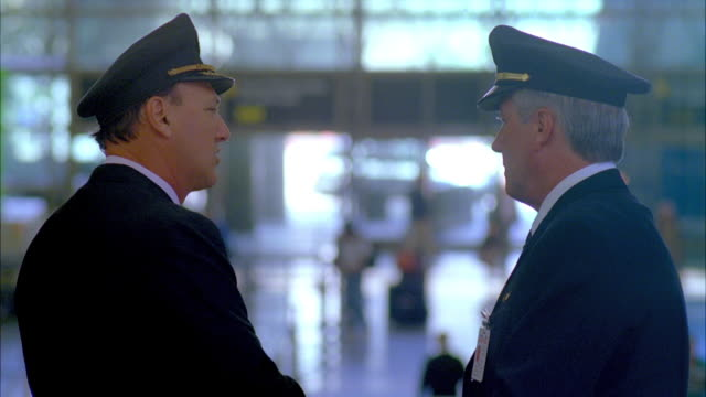 MS R/F Two airline pilots talking in busy airport terminal / Los Angeles, California, USA