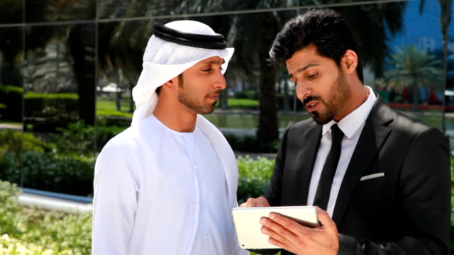 Two arab business people working with digital tablet in the city