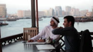 CU MS Two Arab men in traditional and western dress drink tea in outdoor restaurant / Dubai/UAE