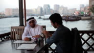 PAN MS two Arab men in traditional and western dress drink tea in outdoor restaurant/Dubai/UAE