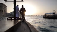 WS Two Arab men in traditional and western dress greet each other on boat in Dubai Creek/Dubai/UAE