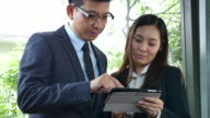 Two Asian business people using Tablet PC