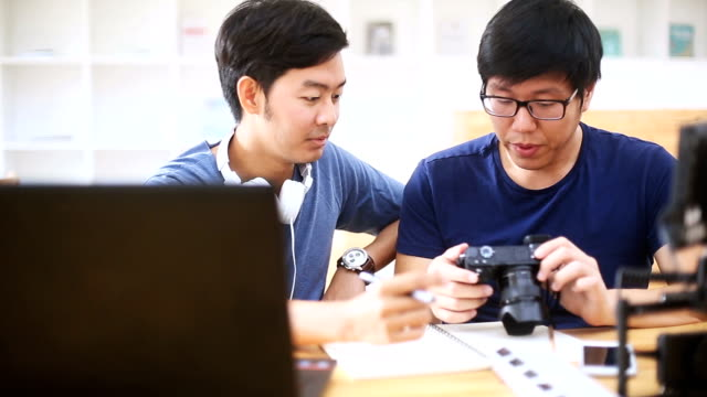 Two Asian Men looking and discussing photos on DSLR