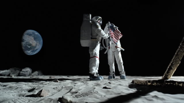 WS SLO MO Two astronauts putting up American flag on moon and saluting / Berlin, Germany